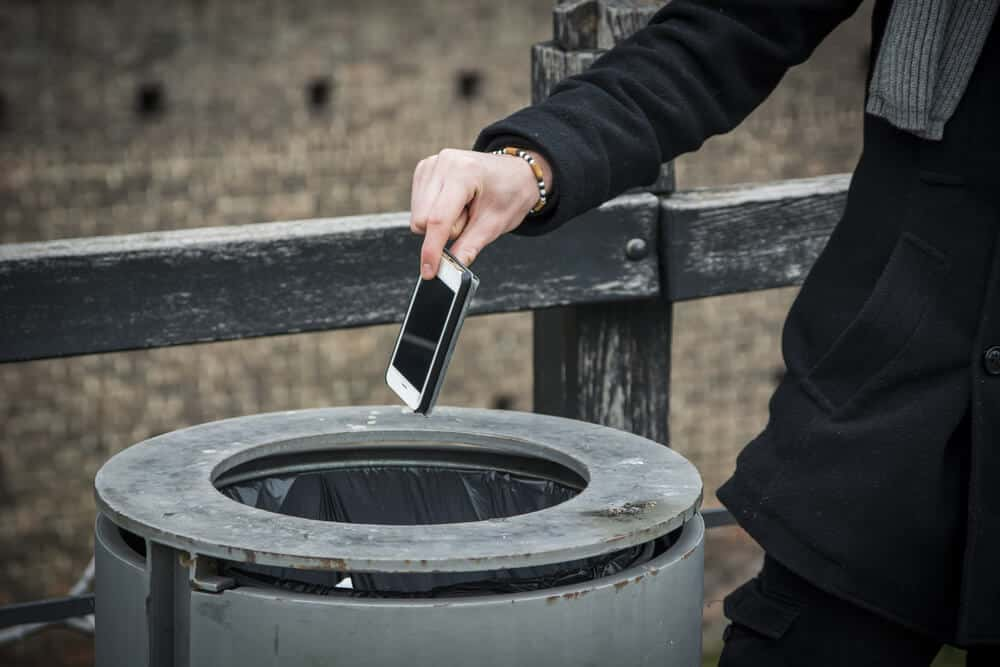 man throwing phone in trashcan